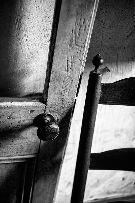 Black and white photograph of an old French-style door and wooden chair inside an old house in Lafayette, Louisiana.