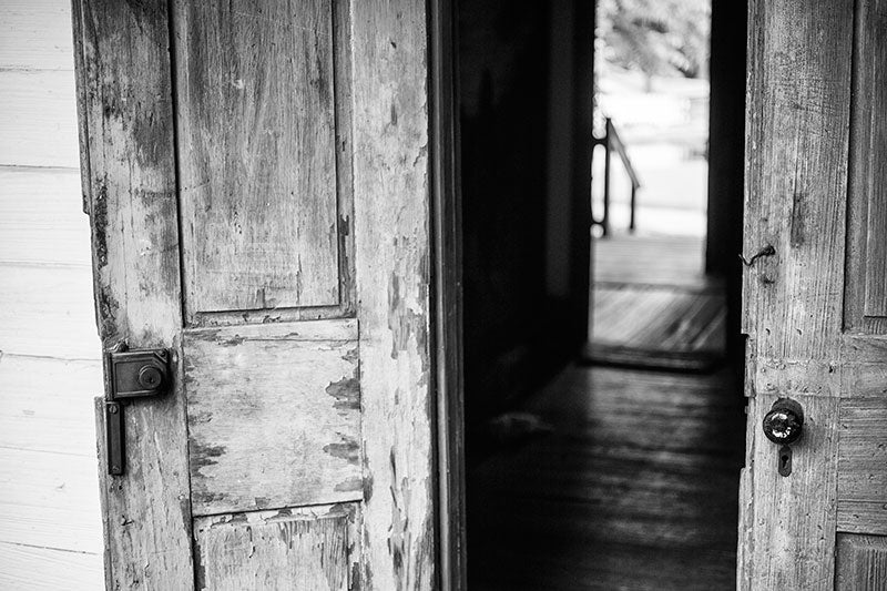 Black and white photograph of French doors on the front of an old Cajun house in Lafayette, Louisiana.