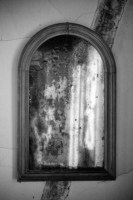 Black and white photograph of a tarnished antique mirror found in an old house in Lafayette, Louisiana.