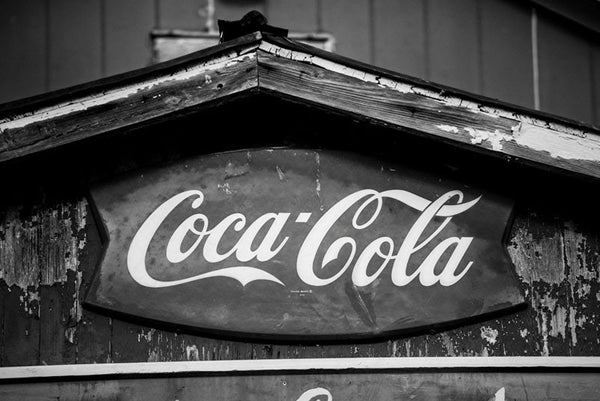 Black and white photograph of a vintage Coca Cola brand sign on a very old building with peeling paint in a small southern town.
