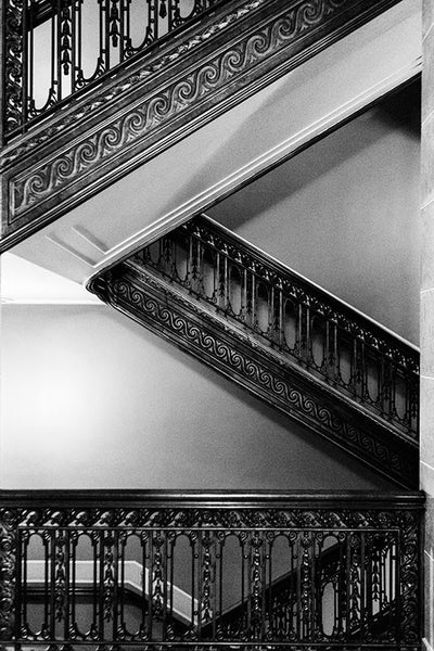 Black and white photographic composition of the ornate staircases inside the historic Wisconsin State Capitol building in downtown Madison, Wisconsin.