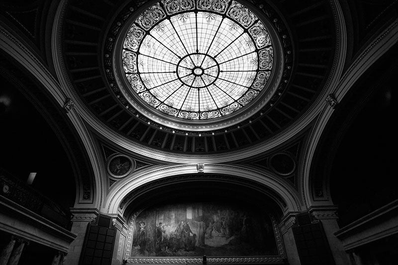 Black and white natural light photograph of a highly ornate assembly room inside the Wisconsin state capitol in Madison, Wisconsin. Because the assembly was not in session, the lights were off in the room, with just natural light from the decorative overhead skylight to illuminate the massive mural at the head of the room.