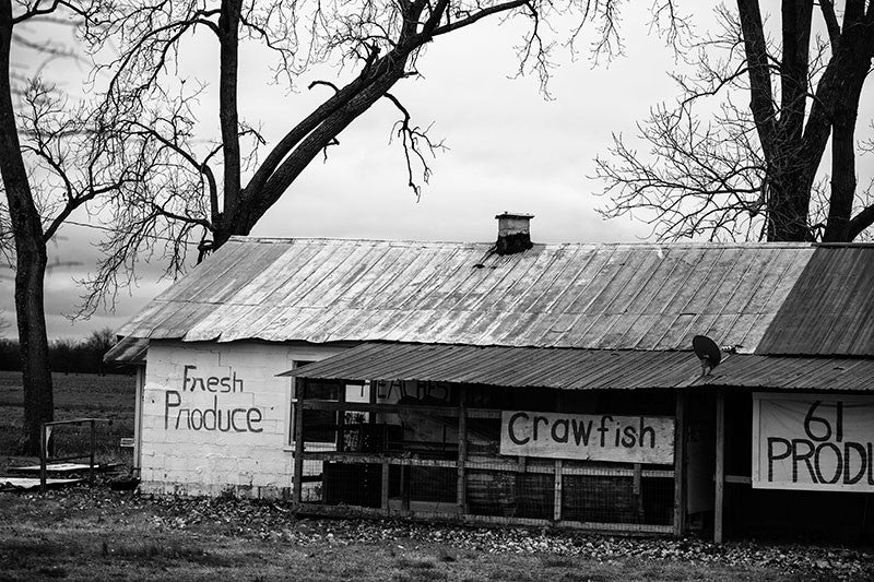 "Black and white photograph of a roadside farm fresh produce stand near Tunica, Mississippi. On the barn are hand-painted signs that say ""Fresh Produce,"" and ""Crawfish."""