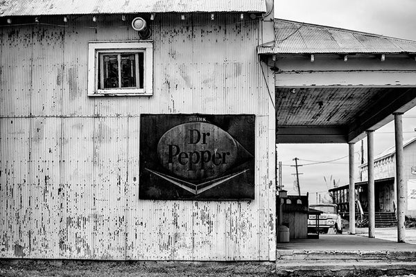 Black and white photograph of an old wood and corrugated steel building near Clarksdale, Mississippi, with a rusty vintage Dr. Pepper sign.