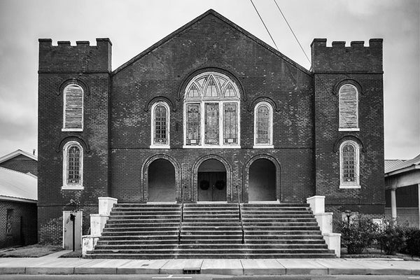Black and white photograph of a historic red brick church in downtown Clarksdale, Mississippi.