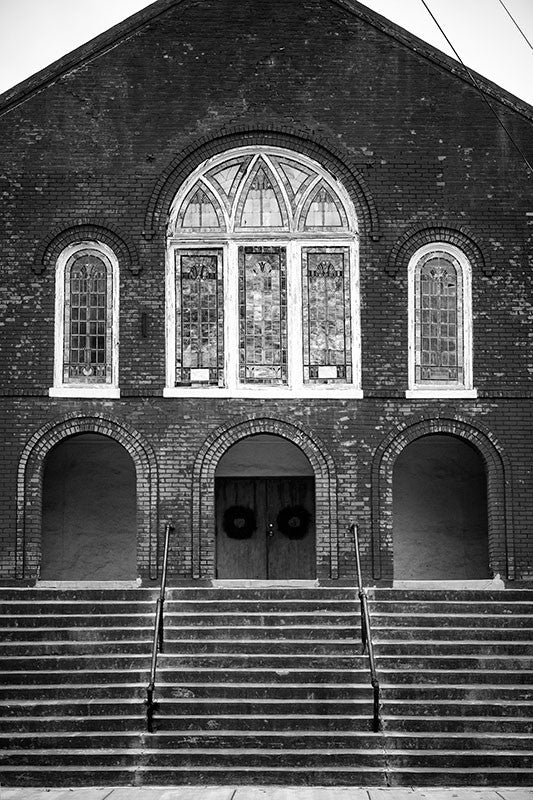 Black and white photograph of the steps and front of a historic red brick church in downtown Clarksdale, Mississippi.