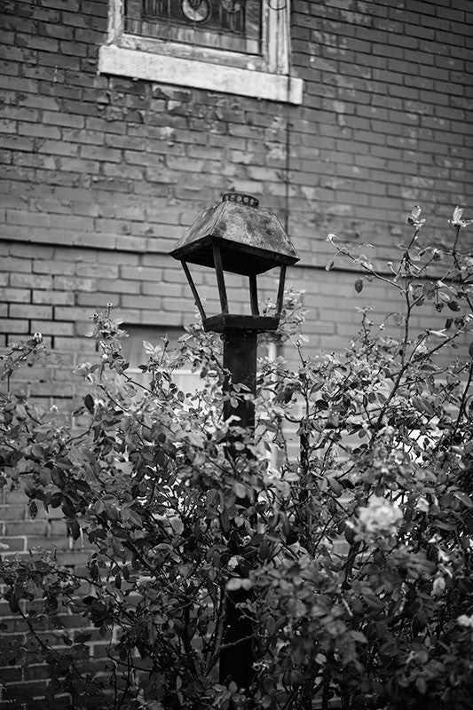 Black and white photograph of a dented lamp in the lawn of a historic red brick church in downtown Clarksdale, Mississippi.