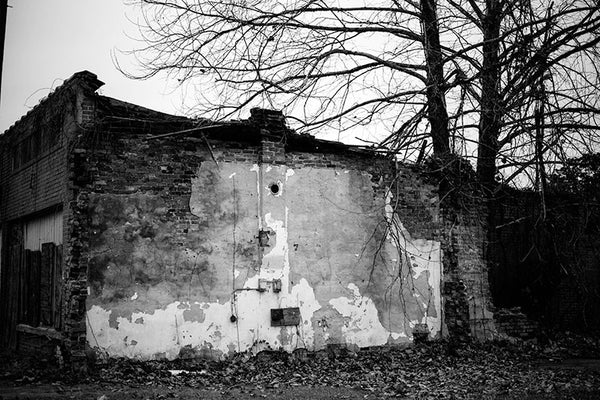 Black and white photograph of an abandoned and boarded-up building in the birthplace of the blues, Clarksdale, Mississippi.