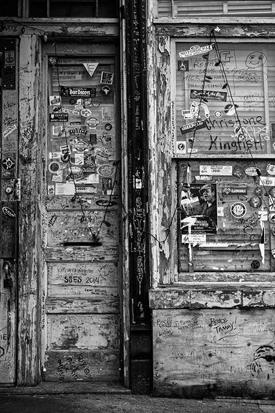 Black and white photograph of the grungy doors at the entrance of a blues club in Clarksdale, Mississippi, the heart of the Mississippi Delta blues region.