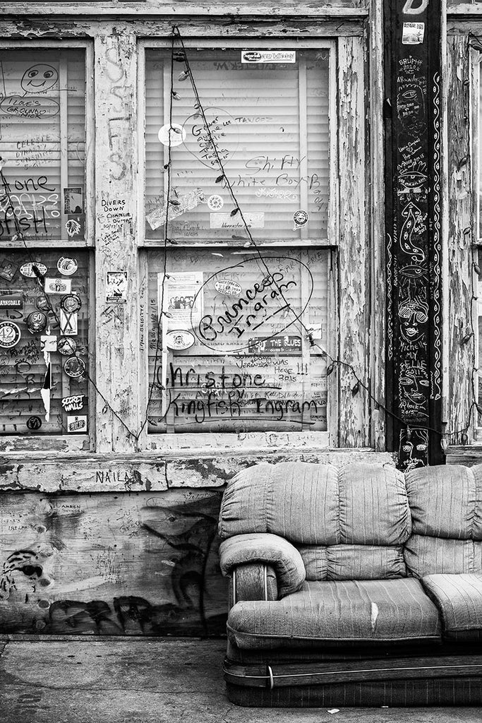 Black and white photograph of the front porch of a downtown Clarksdale, Mississippi, with an old sofa and lots of graffiti.