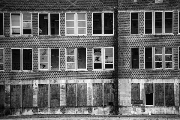 Black and white photograph of rows of broken windows in a very large abandoned school building in Clarksdale, Mississippi.
