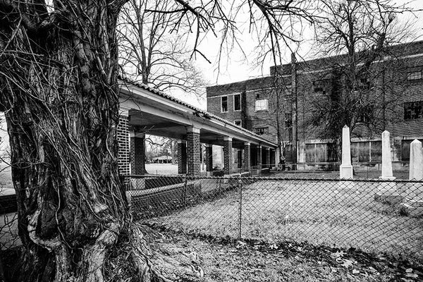 Black and white photograph of a very large abandoned school building in Clarksdale, Mississippi, with the remains on an old family cemetery on the school yard.  NOTE: I had originally, mistakenly called this a confederate cemetery, but it's actually the Bobo family cemetery, with headstones ranging from 1801 to 1895.