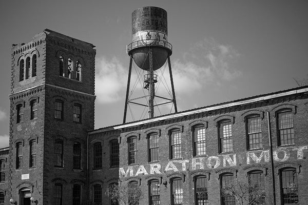 Black and white photograph of the Marathon Motor Works factory in Nashville, Tennessee. Built in 1881 to house the Phoenix Cotton Mill, the Nashville factory was used to manufacture automobiles from 1910 until 1914. The Marathon name was fitting with a Grecian craze that swept the country at the time.
