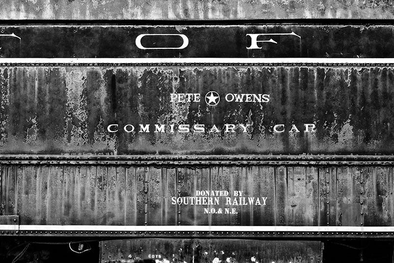 Black and white photograph of an abandoned, rusty and peeling Pete Owens Commissary train car.