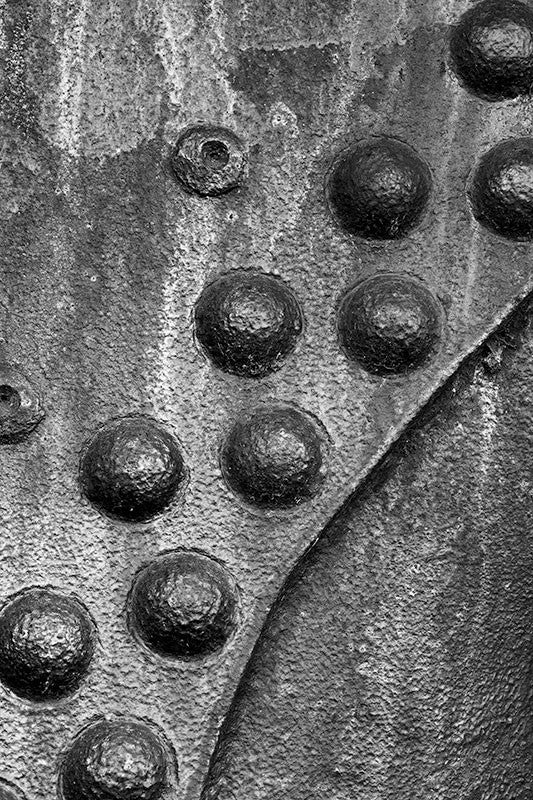 Black and white detail photograph of rusty metal surface with a curved pattern of big rivets.