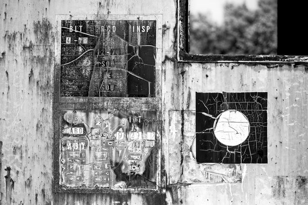 Black and white abstracted photograph of cracked old signs on the side of a rusting abandoned train car.