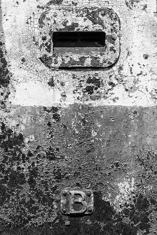 Black and white detail photograph of the beautifully textured, cracked and peeling side of an old train car.