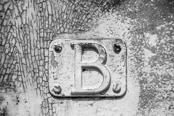 "Black and white detail photograph of metal plate with a letter ""B"" bolted onto the cracked and peeling side of a rusty, abandoned railroad train car."