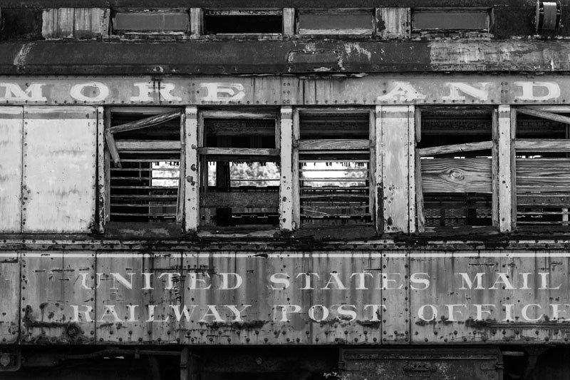 Black and white photograph of an abandoned and dilapidated US Mail train car found in Alabama.