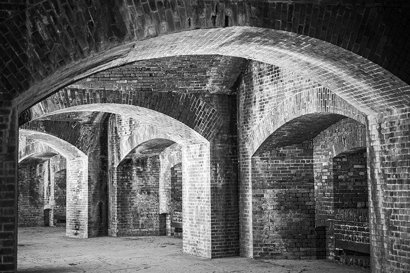 Black and white architectural photograph of the thick, brick arches and niches inside Fort Massachusetts, the Civil War-era fort perched atop the sandy sliver of Ship Island, 12 miles off the coast of Mississippi.