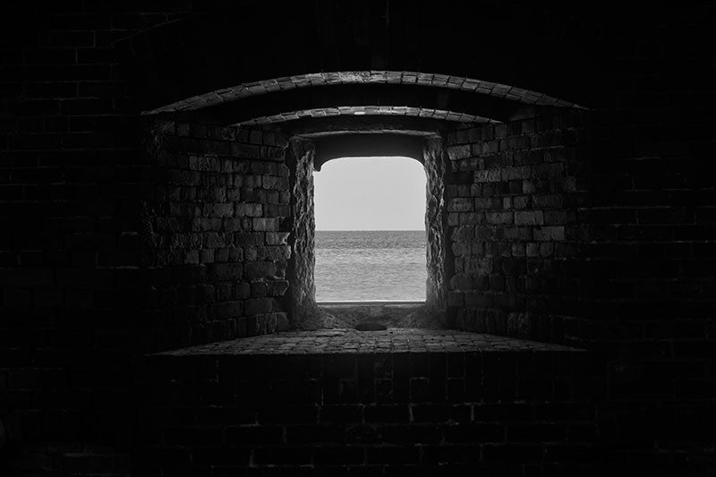 Black and white architectural photograph of the Gulf of Mexico, as seen through one of the heavy brick gun ports at Civil War-era Fort Massachusetts, on Ship Island, Mississippi.