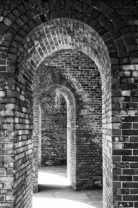 Black and white photograph of a corridor of repeated arched brick doorways, captured in dramatic lighting.