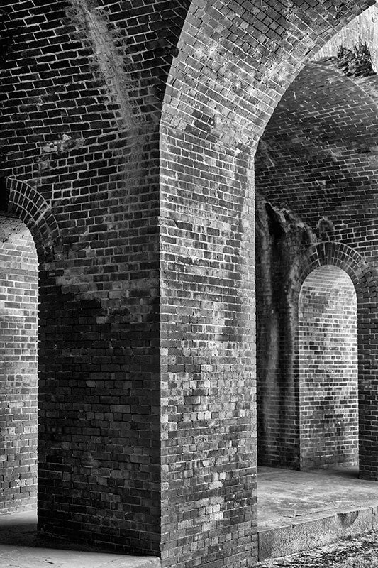 Black and white photograph of thick, brick columns and arches inside an old fort, but resembling something like a castle or dungeon.