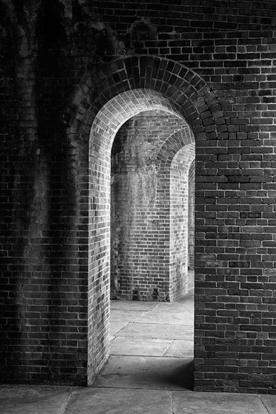 Black and white photograph of thick, brick walls with a series of repeated arched doorways, captured in dramatic lighting.
