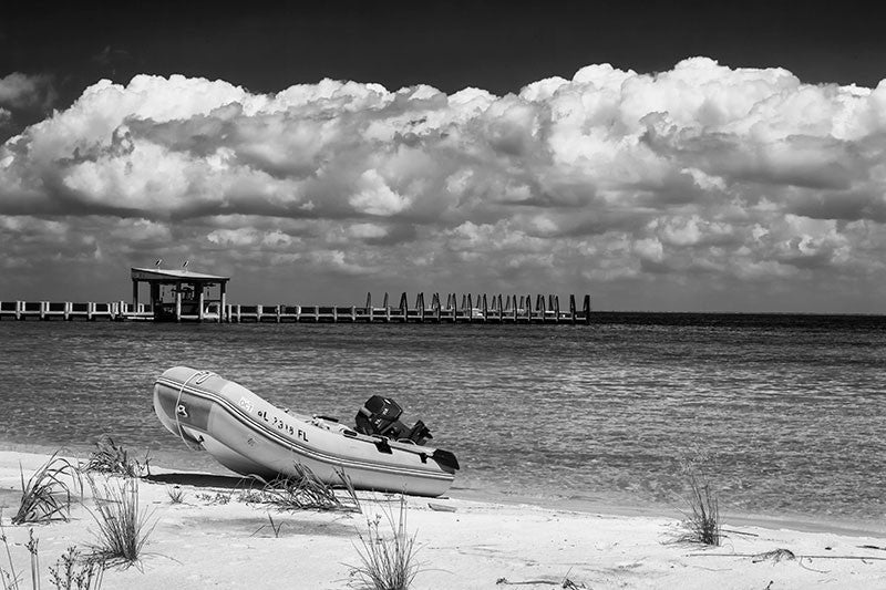 Black and white photograph of a boat pulled ashore on an island in the Gulf of Mexico off the coast of Mississippi, with a huge bank of clouds on the horizon.