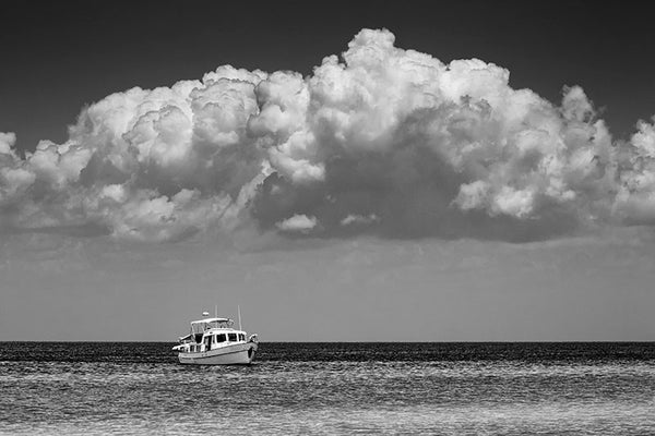 Black and white photograph of a boat anchored near an island in the Gulf of Mexico off the coast of Mississippi, with a huge bank of clouds over head.