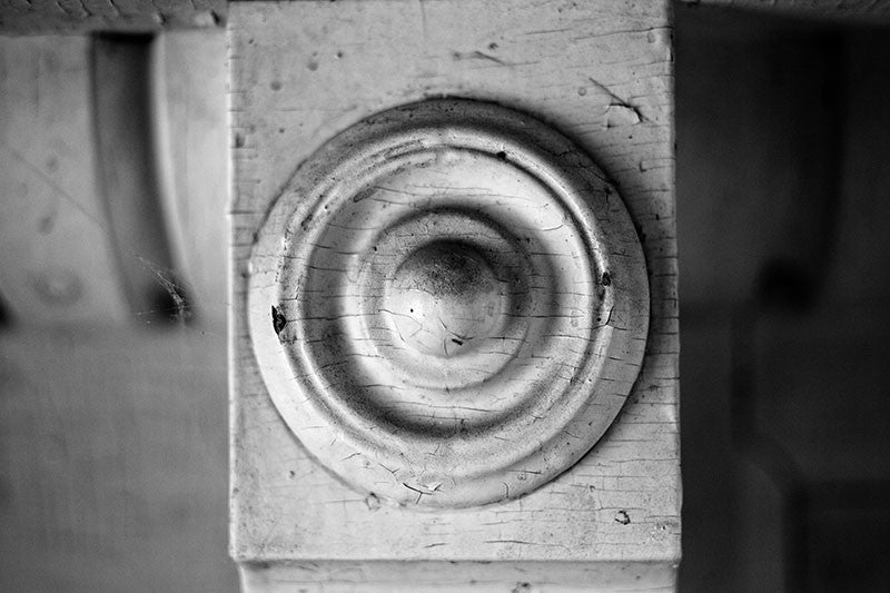 Black and white detail photo of an antique wooden fireplace mantel from an old southern home.