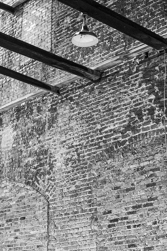 Black and white industrial photograph of an old brick warehouse with a missing roof.