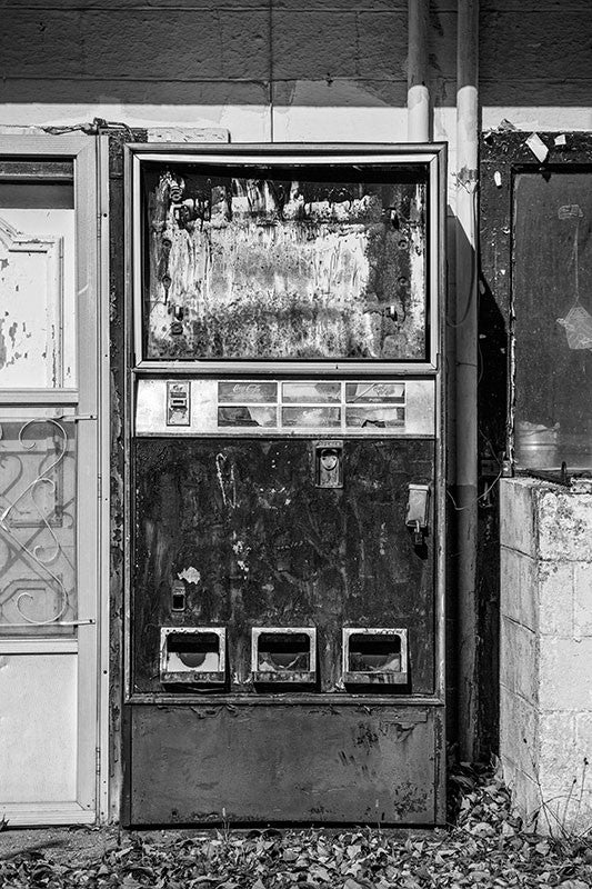 Black and white photograph of a textured, broken, and abandoned vending machine found along the side of a country road.