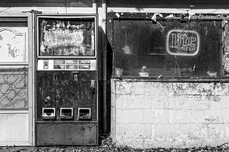 Black and white photograph of an abandoned bar and vending machine found along a country highway.