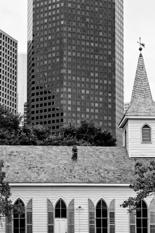 Black and white photograph of a small wooden historic church among the towering glass skyscrapers of downtown Houston.