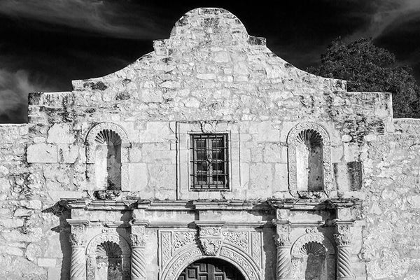 "Black and white fine art photograph of the unmistakable front façade one of the most recognizable buildings in the world, the Alamo in San Antonio, Texas. The Alamo is one of San Antonio's old Spanish missions, built as the Misión San Antonio de Valero in 1744. It gained notoriety in 1836, when a small group of Texas freedom fighters (then called Texians), took refuge in the mission for a battle against overwhelming Mexican forces under General Antonio Lopez de Santa Anna. ""Remember the Alamo,"" became a ral"