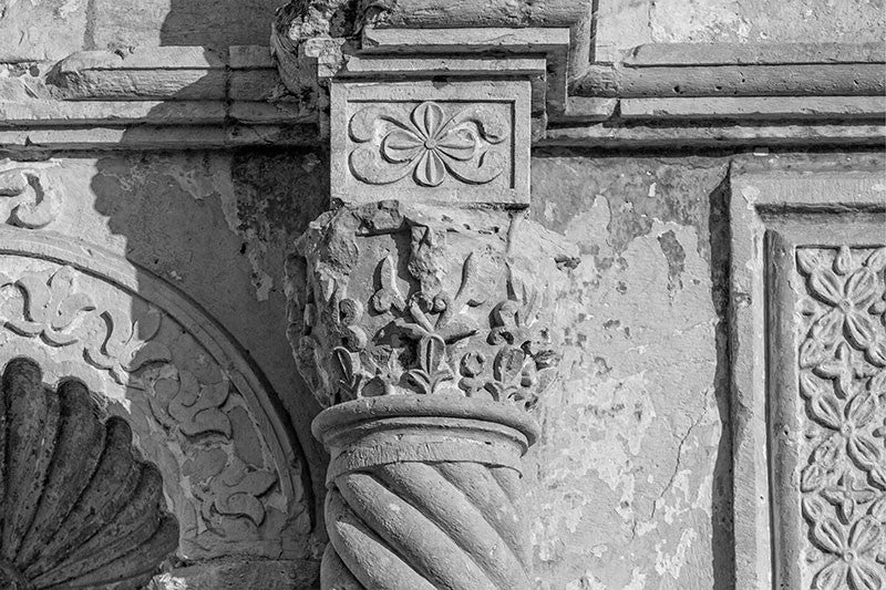 Black and white detail photograph of one of the carved stone columns on the front of the world-famous Alamo in San Antonio, Texas