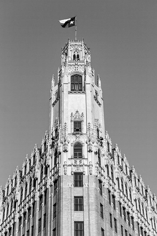 "Black and white fine art architectural photograph of the Texas flag flying over The Emily Morgan Hotel in San Antonio, Texas. Built in 1924 to serve as a medical arts building, the iconic Gothic Revival building is now a hotel named after a heroine of Texas history, Emily Morgan (also known as Emily D. West), who was also the inspiration for the song ""The Yellow Rose of Texas."""