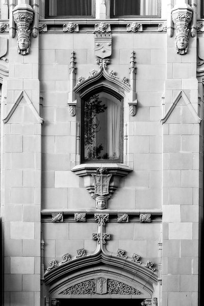 Black and white architectural photograph of the ornate Gothic Revival details on the exterior of The Emily Morgan Hotel in San Antonio, Texas. Details include several human faces carved into the stone work.