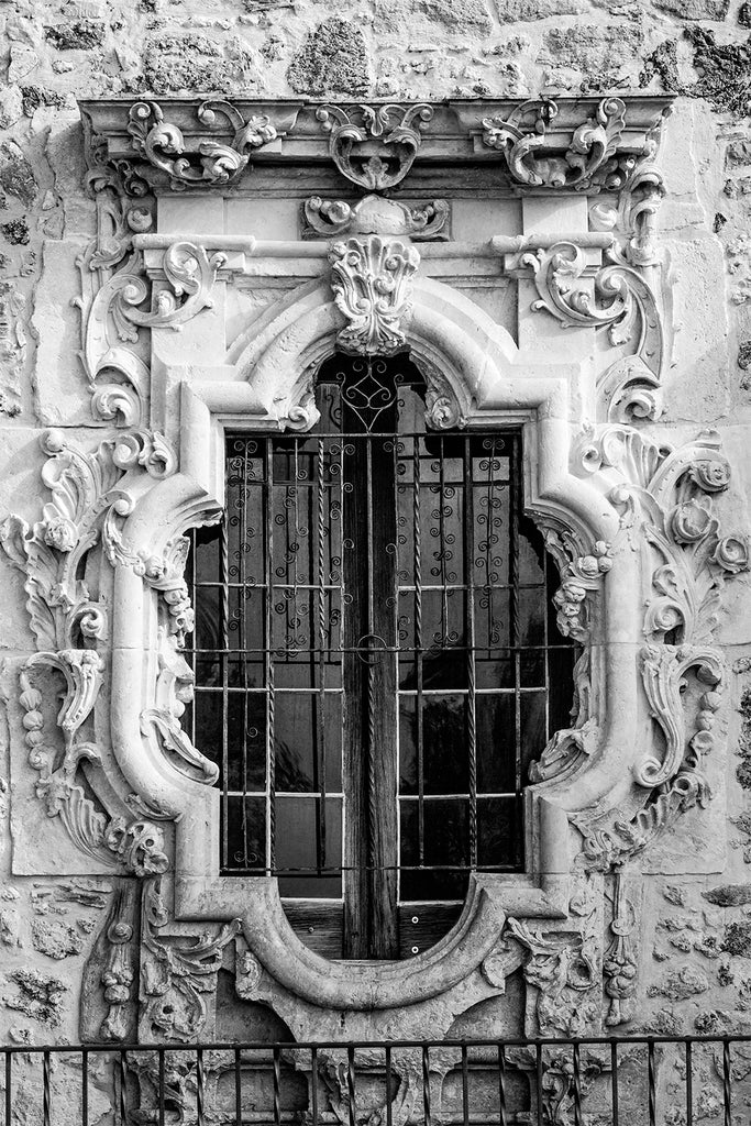 Detailed black and white fine art photograph of the famous Rose Window outside the church sacristy of Mission San Jose in San Antonio.