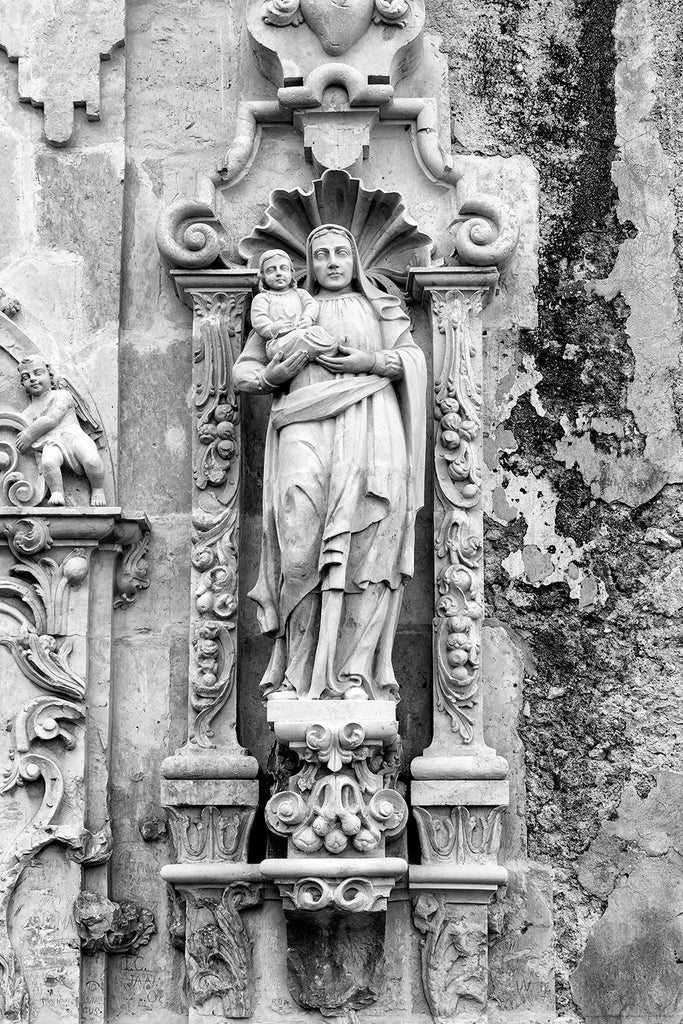 Black and white fine art photograph of the carved stone sculpture of St. Anne with Mary on the limestone exterior on the old Spanish Mission San Jose in San Antonio.
