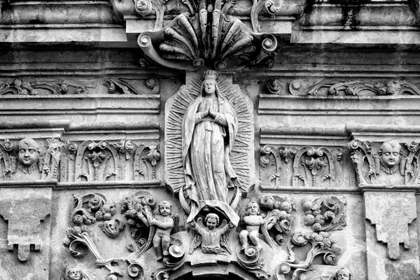 Black and white fine art photograph of the ornate carved stone relief sculpture on the exterior on the old Spanish Mission San José in San Antonio, Texas.