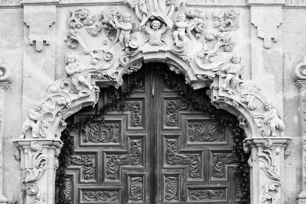 Black and white photograph of of the beautifully ornate hand-carved wooden doors at Mission San Jose in San Antonio, Texas. Around the carved doors is a framework of carved limestone reliefs featuring cherubic angels.