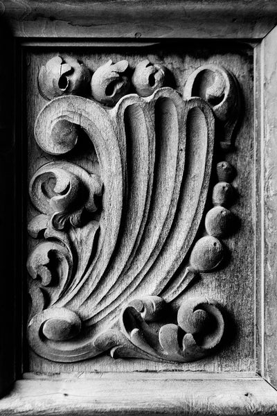 Black and white photograph of one of the rustic hand-carved wooden chapel doors at Mission San Jose in San Antonio, Texas. The wave motif may symbolize the ocean voyage that delivered the missionaries from Spain to the new world.