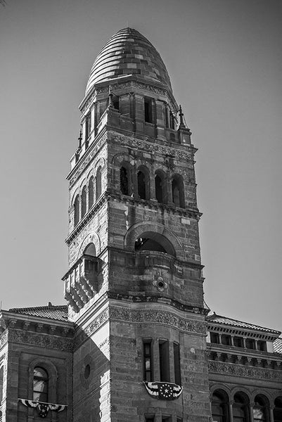 Black and white photograph of the tower of Bexar County Courthouse, a red sandstone building opened in 1896. Designed in the Romanesque revival style by architect James Riley Gordon, the courthouse sits in San Antonio's Main Square, adjacent to the historic Cathedral of San Fernando.