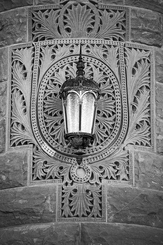 Black and white photograph of a lamp on the ornately patterned stone of the old Bexar County Courthouse in San Antonio.