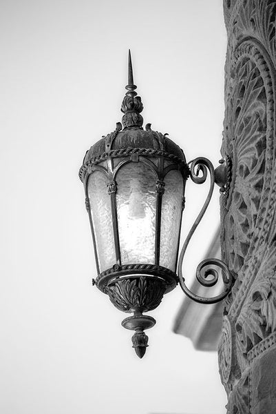 Black and white architectural detail photograph of a lamp on the red sandstone exterior of the old Bexar County Courthouse in San Antonio, which opened in 1896.