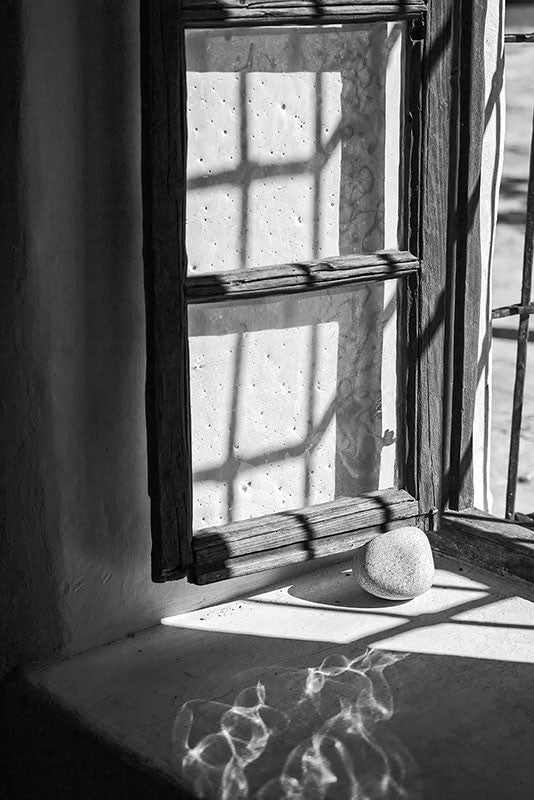 Black and white photograph of a 260-year-old window, propped open with a stone, at The Spanish Governor's Palace in San Antonio, Texas.
