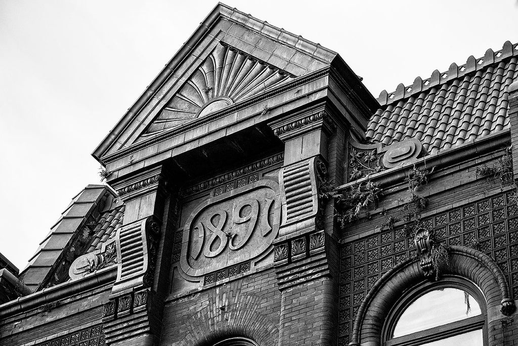 "Black and white photograph of an ornate building with a stylized date that says ""1891,"" located on King Street in Charleston, South Carolina."