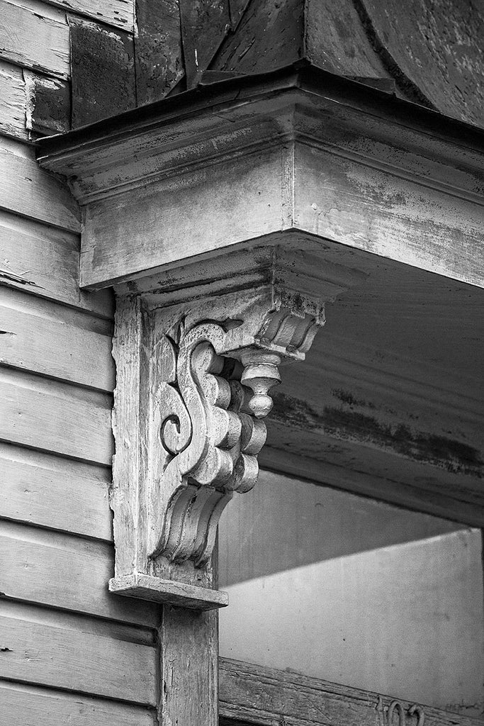 Black and white architectural detail photograph of antique wooden corbel under the eave of a porch an old house in Charleston, South Carolina.